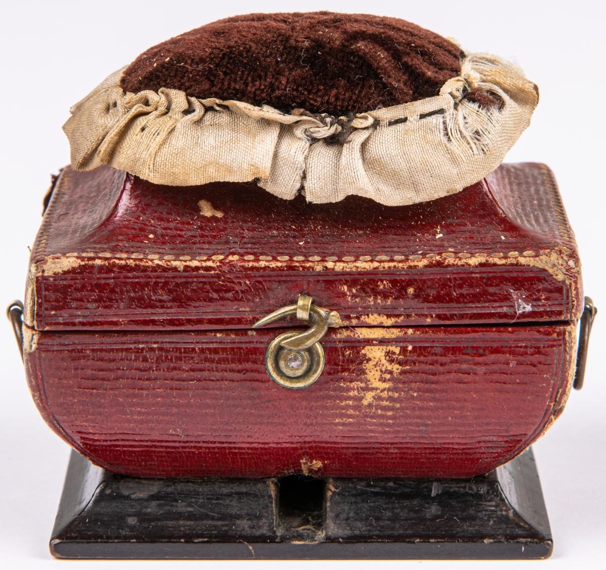 Sybaron, röd pappask med spegel m.m. Chagrin. Askens storlek 4,5x6cm. Kistformig. På undersidan skrivet Marie Ann Wennberg.
