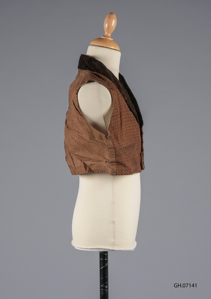 Vest i brunt tekstil av bomull og fløyel. Forstykket er blomstermønstret på utsiden og fôret med bomullslerret på innsiden. Bakstykket er i tynt bomull og er lappet i midten. Kragen er i fløyel. Den har to forlommer. Den lukkes med 5 knapper.