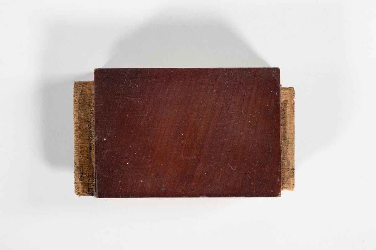 Kort list til sengekrone med fjær i hver ende. På baksiden er en kloss som er limt på. Klossen er delt i to.