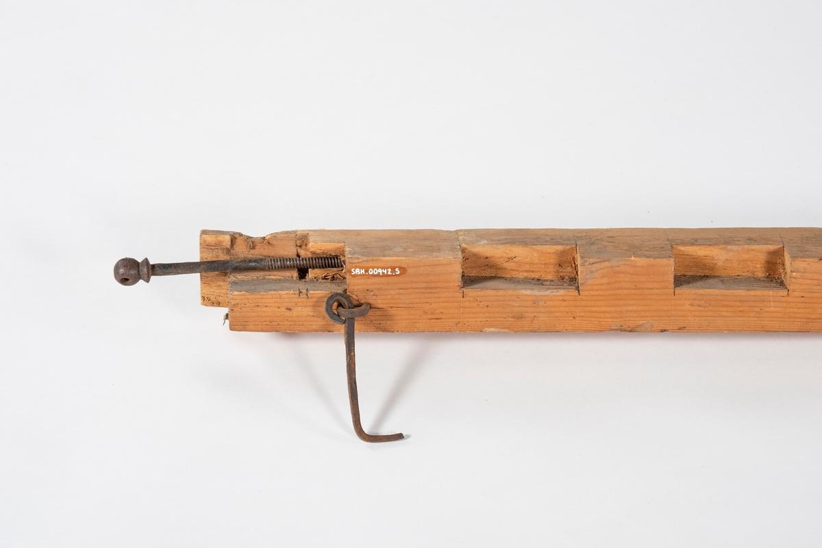 En del av en sengekarm med utskåret spor for bunnplanker. Ved den ene enden er det en jernkrok.