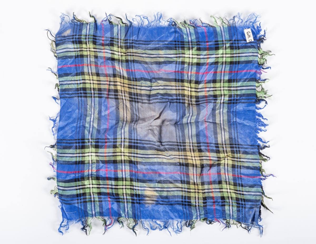 Firkantet tørkle med rutemønster i grønn, blå, rød, svart og hvit. Tørkleet har frynsekant.