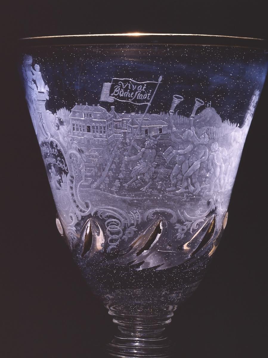 """Avbildet et Bacchustog og prospekter av gårdene Bogstad, Mælum og Buskerud (på Modum). Bacchustogets heraldiske dyr viser til familievåpen: Leuch: Geitebukk med løk i hånden (Bogstad), Darjes: Griff (Mælum) og Collett: Hjort (Buskerud på Modum).  Beskrivelse fra """"Gammelt norsk glass"""", Ada B. Polak, 1953, s. 293: """"Gravert fors.: rokokkoramme, hvori amorin som slår sirkel med passer med parklandskap som bakgrunn; over: Kjerlighed / haver ingen Ende; om resten av klokken Bacchustog: satyr, 2 putti som blåser på lur, en putto med tromme på ryggen, en annen som trakterer den, naken mann og kvinne med hver sin vinstokk, vinløvkranset Bacchus ridende på geit, en satyr drar geita, to andre støtter den drukne Bacchus, to par putti som bærer drueklaser, hengende fra stokker over sine skuldre, satyr, geit med løk i hånden, griff, hind; i bakgrunnen landskap hvori tre gårder; første og siste satyr og en av drueklasebærerne holder bannere, som flyr over hver av gårdene; på banneret over første Vivat / Buchestad, over den annen Mæhlum og, over den tredje Buscherud. Under rokokkoverk;under første satyr signatur: H G K 1764. Lokk: rokokkoverk hvori innflettet tre drukne putti i hvert sitt felt; et fjerde felt er tomt; fotpl.: stilisert, slynget vinranke med drueklaser."""""""