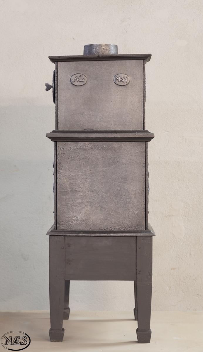Kokeovn med to muser på enkel profillist. En fløytespillende og en dansende. Begge med draperier. Kokeanretning i topplaten til 1.etg. Ovnsdør på kortside. Rosett på begge sideplatene 2.etg. Den ene er løs og fungerer som ventil. Innskrift på frontplate og bakplate 2.etg. Røykuttak i toppen.