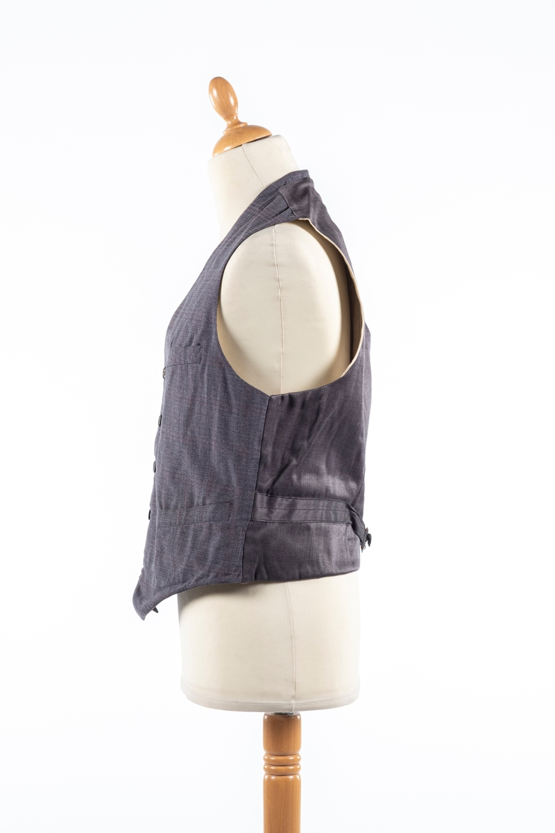 Vest med forstykke i grå rutete ullstoff og bakstykke i grå silke. Den har foring i stripete stoff. Den lukkes i front med fem knapper og har spensel i ryggen. Vesten har fire forlommer og en innerlomme.