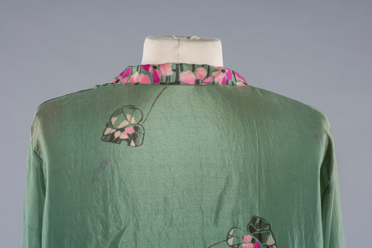 En grønn silkekjole med rosa blomstermønster i Charleston-fasong. Den har lange ermer og V-ringet halsåpning. Ermene er i krepp.chiffon. Mansjettene er smale med trykknapper. Det er svarte stofftrukne pynteknapper i halsåpningen. På sidene er stoffet rynket med påsydd spensel og 2 stofftrukne pynteknapper i sort.