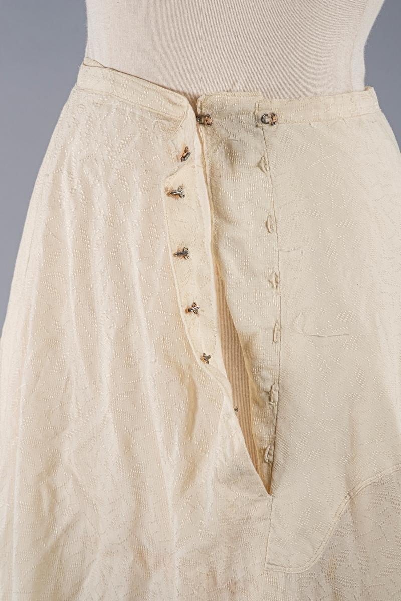 Kremfarget skjørt med slep. Stoffet har vevd mønster og foringen er av lin (?). Den lukkes med metallhekter på venstre side. På innsiden av linningen i midjen er det en hemp bak for hekting av kjoleliv.