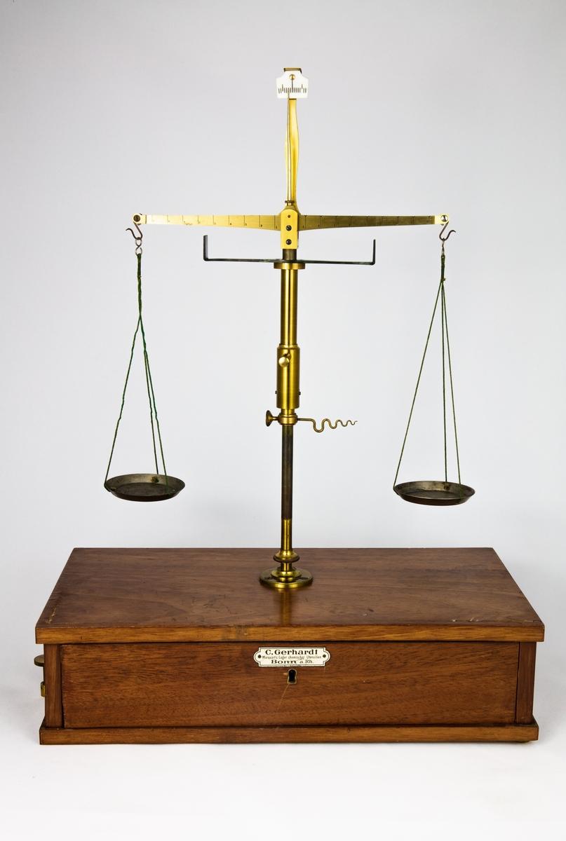 En våg på träsockel med låda i för tillbehör. Nyckel saknas till lådan.  Vågen är använd inom den kemiska undervisningen för att kunna bestämma vikten av ett ämne eller objekt. Det man ville väga placerades i den ena vågskålen och i den andra lades vikter för att beräkna föremålets vikt. När vågen var i balans motsvarade föremålets vikt i viktskålen.