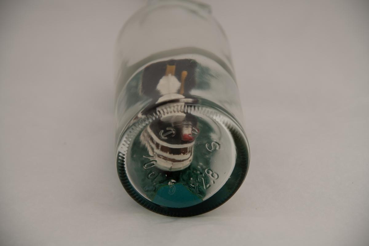 """Flaskeskute: """"Pelle"""" av Arendal.  Glass, svakt blågrønt, lukket med røft lakk. Flaskeskute bygget av  tre, bambus, knappenåler, og malt. Vinduer av plast. D/S """"Pelle"""" hvitmalt med sort overdekk, gul skorstein med sort øverst, hvit livbåt, to hvite og røde nødraketter. Brunlakket passasjerdekk. Grønnblå, toppet sjø. Flaske med sirkulært merke for etikett på skulderen. En ring om halsen, har hatt skrukork: gjenger øverst. Innstemplet i flaskebunnen:  70 CL,"""
