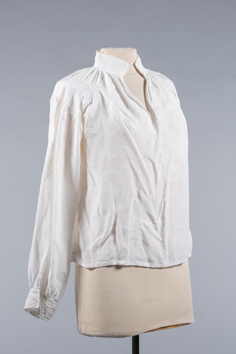Skjorte i hvit lin. Den har høy hals med splitt/åpning i front og lange ermer. Det er broderier på halskragen og mansjettene. Skjorten har bærestykke over skuldrene. Ermene har piperynker mot mansjettene. Mansjettene har to knappehull.