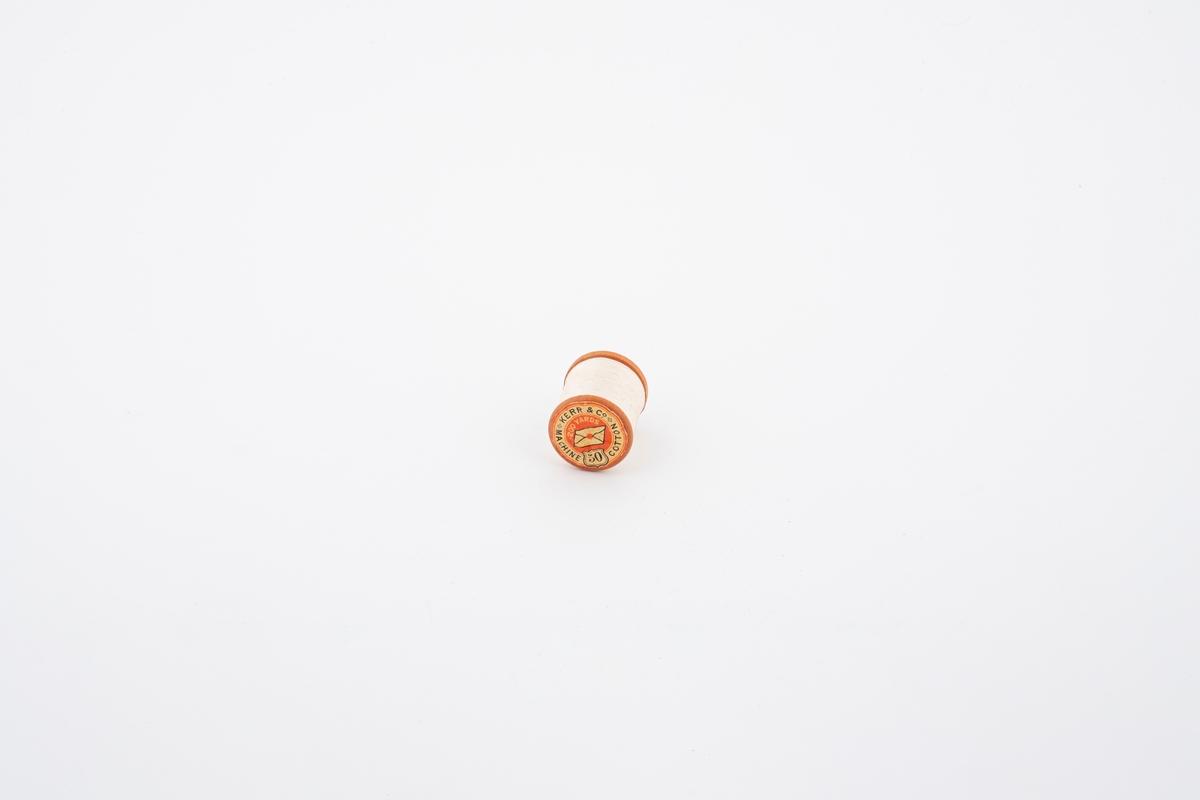 En snelle av tre med hvit sytråd. Det er påklistret varemerke på begge ender av snellen.