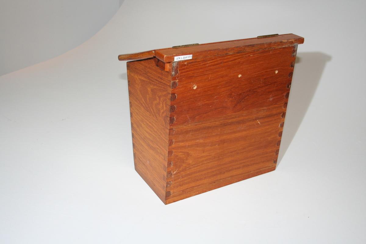 Kassen er lakkert og kledd med filt på innsiden. Filten er litt slitt i sidene. Lokket er hengslet fast i kassen med to hengsler i overkant. Det er tre hull i bakplaten for å kunne skru den fast til veggen. En skrue sitter fortsatt i.  I bunnen ligger det myk isopor og en slingerduk.