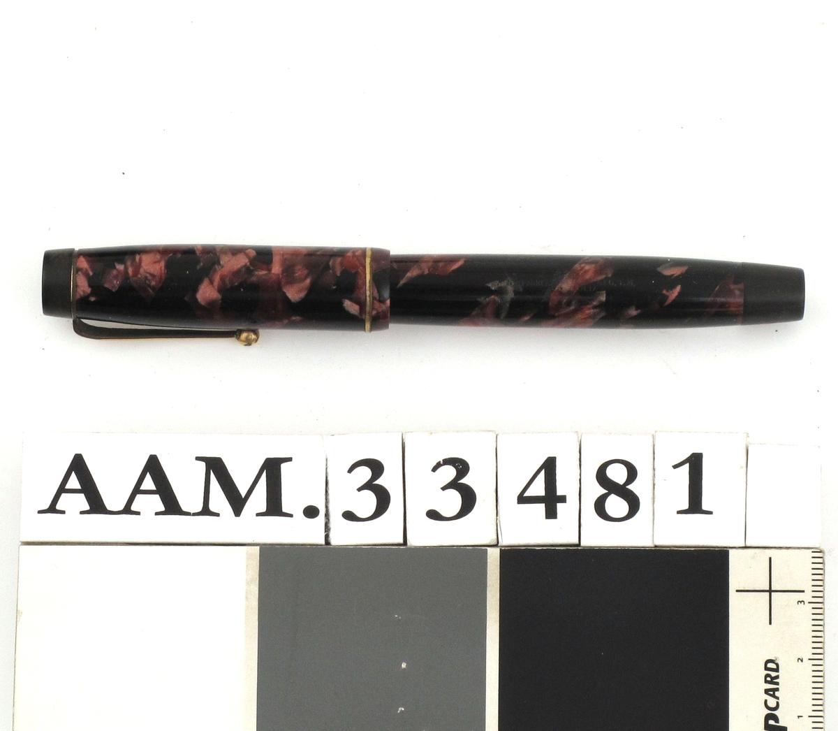 Fyllepenn, sort med mønster i rosavalører. Pennen inneholder en beholder og blekk suges opp i beholderen fra et blekkhus.