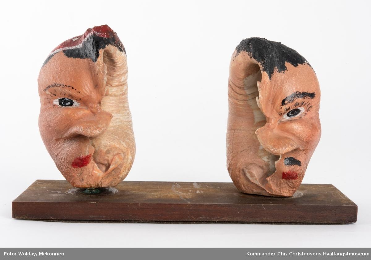 To bemalte øreknokler montert løst på en plate. De er malt som hode til en mann og en dame.