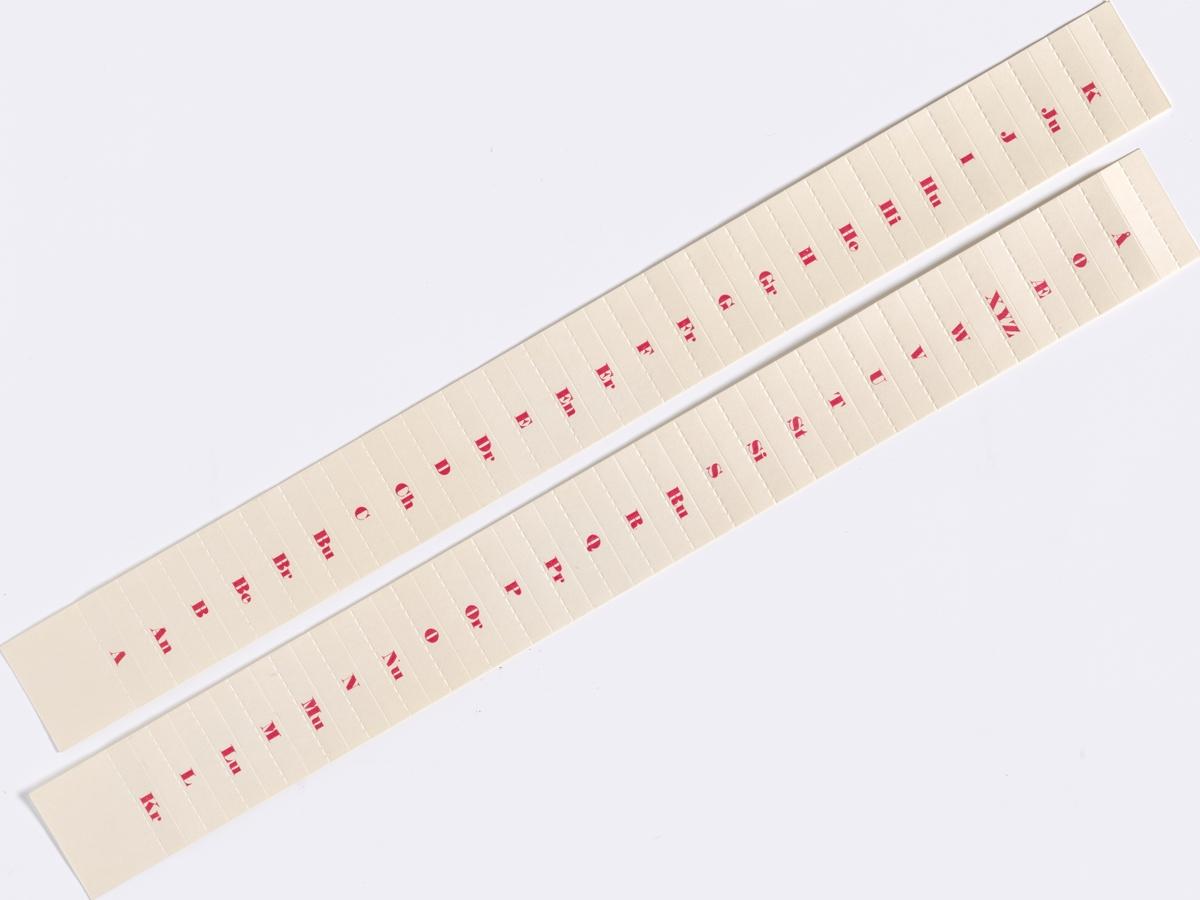 To remser med merkelapper med røde bokstaver fra A til Å. Noen av merkelappene har flere bokstaver.  NAV-samlingen er en gruppe av gjenstander som har vært anvendt på sosialkontoret (Aetat - NAV) i Skedsmo kommune.