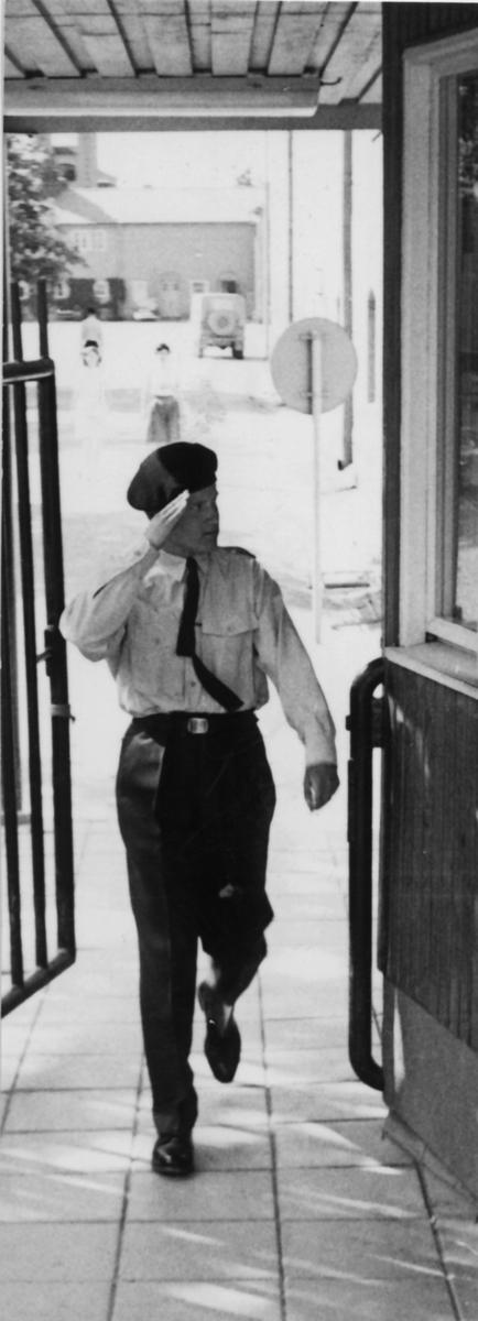 Kasernvakten, omkring 1980  Vakten låg ursprungligen i by 008 -- mitt över kaserngården från kanslihuset. När biltrafiken ökade på slutet av 50-talet blev det opraktiskt med den snäva kurvan in genom grind 1, så vakten flyttades till kasern 004. Muren över Bataljonsgatan ersattes med staket och motordriven körgrind (grind 2) och gånggrind närmast vaktlokalen.  Bild 1: Denna vy mötte man från Regementsgatan. Bilarna som parkerats mot kasern 003 tillhörde vakten och beredkapsstyrkan. Bild 2: Här ser vi vakten och genom staketet ser vi också ingången till vaktens dagrum. Tre av de sex fönstren till arresterna syns också. Bild 3: Vaktchefen kontrollerar id-handling. Bild 4: Under hälsningspliktens tid hälsade man alltid vid in- och utträde.  Under sent 80-tal flyttades vakten återigen, nu till nybyggnad vid kasern 003.