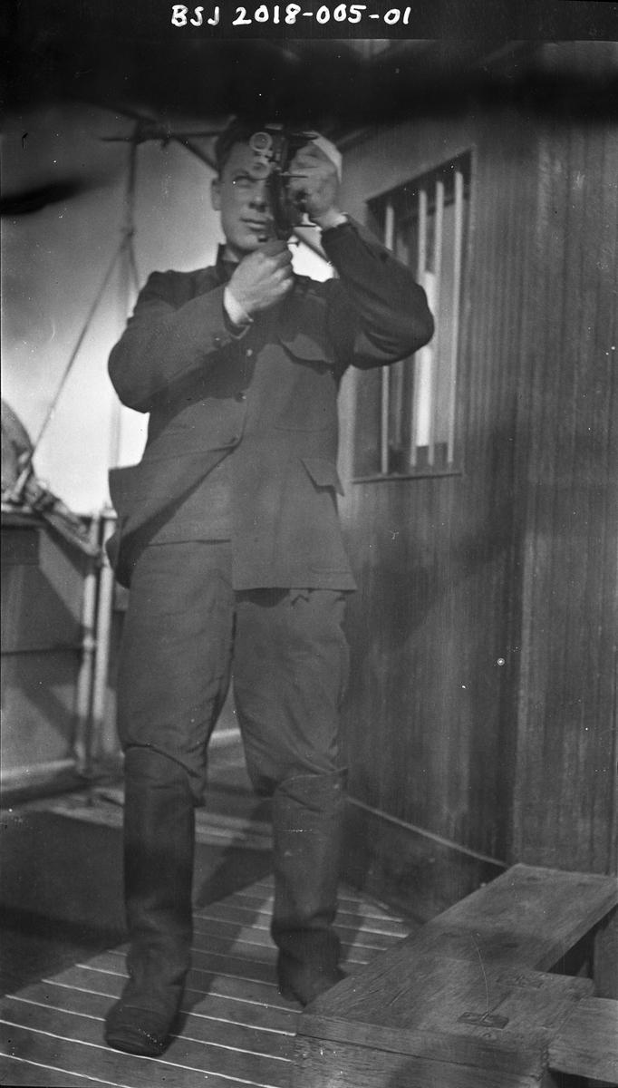 Styrmann Ferdinand Waage ved styrhuset, han tar ut kurs med en sekstant.