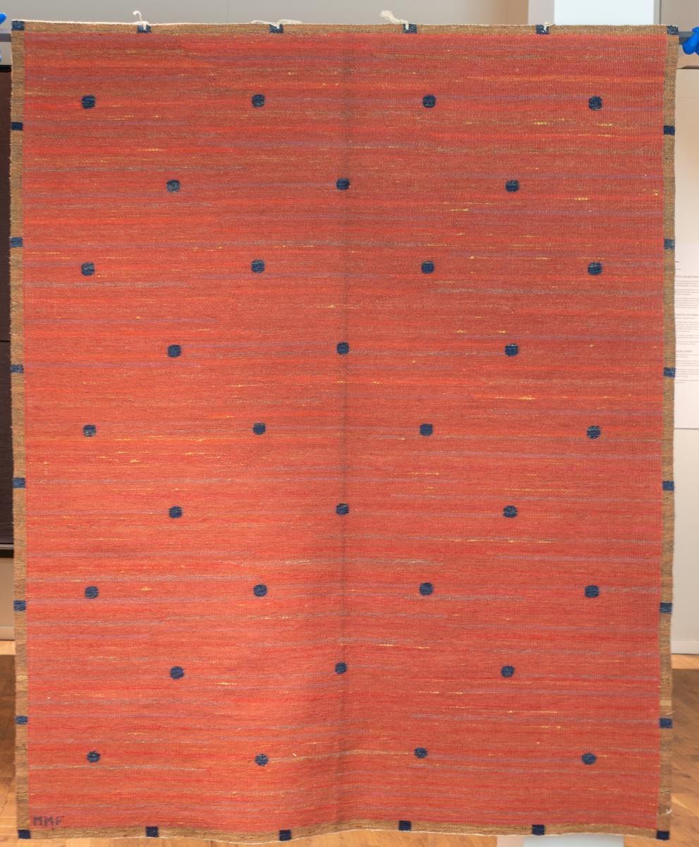Röd duk i rölakan, komponerad före 1919 i Vittsjö. Varp vitt lingarn. Botten i rött ullgarn, insprängt med rödviolett, gulbrunt och grått. De ytterst sparsamma mönsterformerna, blå moucher, i blått. Sign. MMF. Varp: 4 tr/cm            Inslag: ca 9/cm Varp vitt ullgarn, inslag brunt, 2 nyanser gulbrunt, blått, mörkblått, ljusbrunt, rödgult, gulrött, brunrött, rödblått, grått och gult ullgarn troligen 1 tr, röllakan. Mittpartiet små runda former i mörkblått jämnt fördelade över väven mot en botten i flera nyanser rött och inplockade trådar i gult fördelade över väven, runt omkring en smal fyrkantig bård i gulbrunt med små kvadrater i mörkblått jämnt fördelade över bården. Väven avslutas med s.k. falsk stadkant.  Vid ena hörnet invävd signatur MMF i blått ullgarn.  Ett ca 10 cm brett vitt tygstycke i bomull, tuskaft, fastsydd på avigsidan längs ena kortsidan.  4 st snören fastknutna längs ena kortsidan.