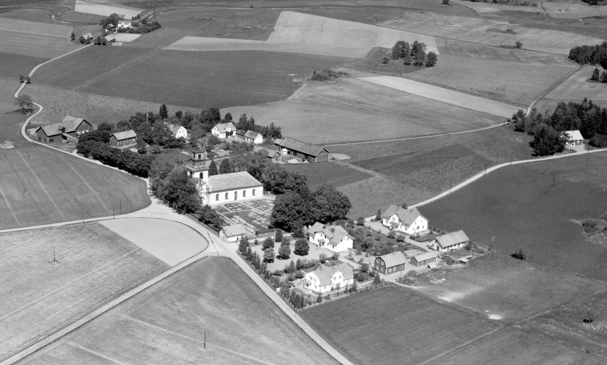 Flygfoto över Rystad kyrkby. Församlingens kyrka förstorades i slutet av 1700-talet efter sammanslagning med grannsocknen Näsby 1780. Arbetet med den nya kyrkan komplicerades av stridigheter med byggmästaren och kunde inte invigas förrän den 23 oktober 1796. De bägge större husen hitom kyrkan fungerade vid tiden för bilden som socknens skola respektive ålderdomshem.