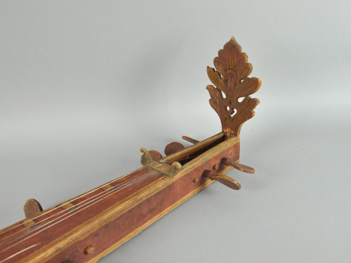 Langeleik av gudbrandsdalstype, med utskåret endestykke som har en inskripsjon på baksiden. Åtte strengeskruer av tre, hvorav den ene er brukket. Utskåret rose midt på kassen.