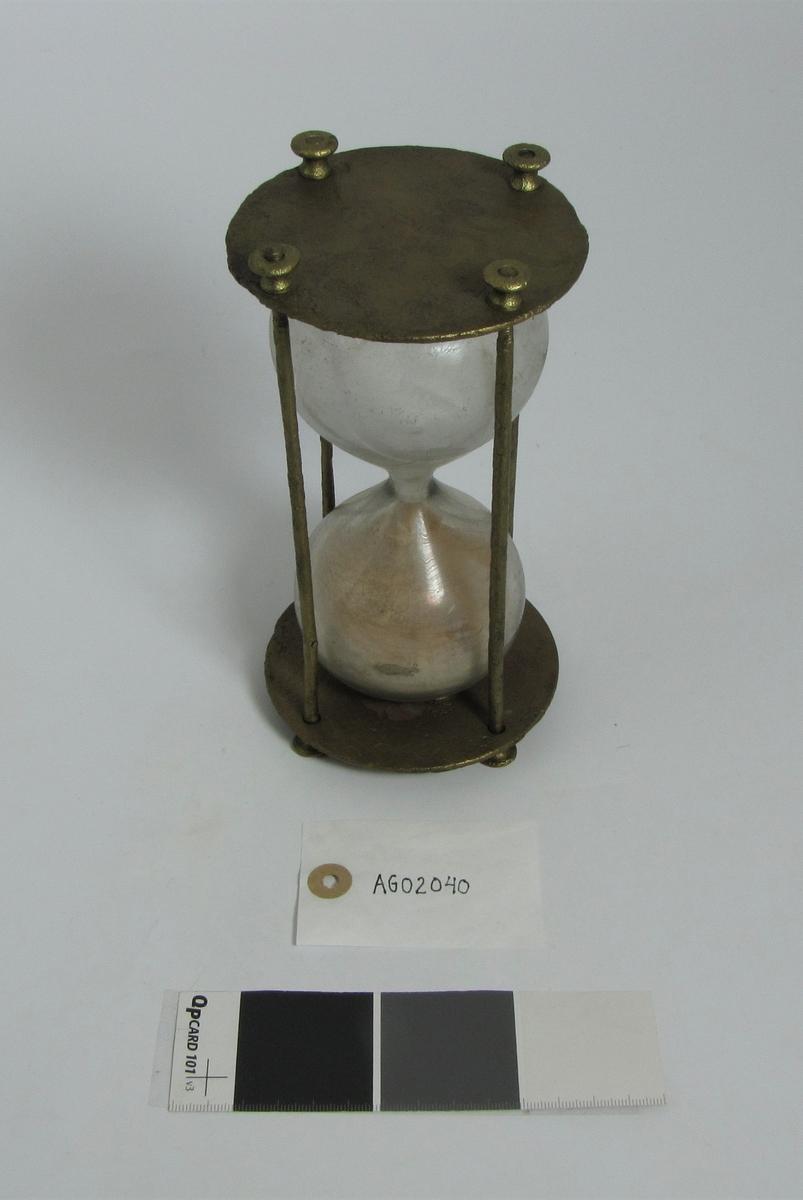 """Logglasset består av et stativ i messing med plate i topp og bunn og fire stenger med gjenger i ene enden. Muttere er skrudd over den ene plata og lodda over den andre. I midten håndblåst glass. Glasset har """"timeglassform"""". Inni glasser er det rødbrun finkorna sand.   I 2020, etter 110 år på havets bunn og 27 år på museet, bruker sanden ca 1-1 1/2 minutt på å renne gjennom glasset.   Dette er trolig et logglass som ble brukt til å beregne skipets hastighet sammen med øvrig loggustyr (loggrull, loggline og loggflyndre)"""