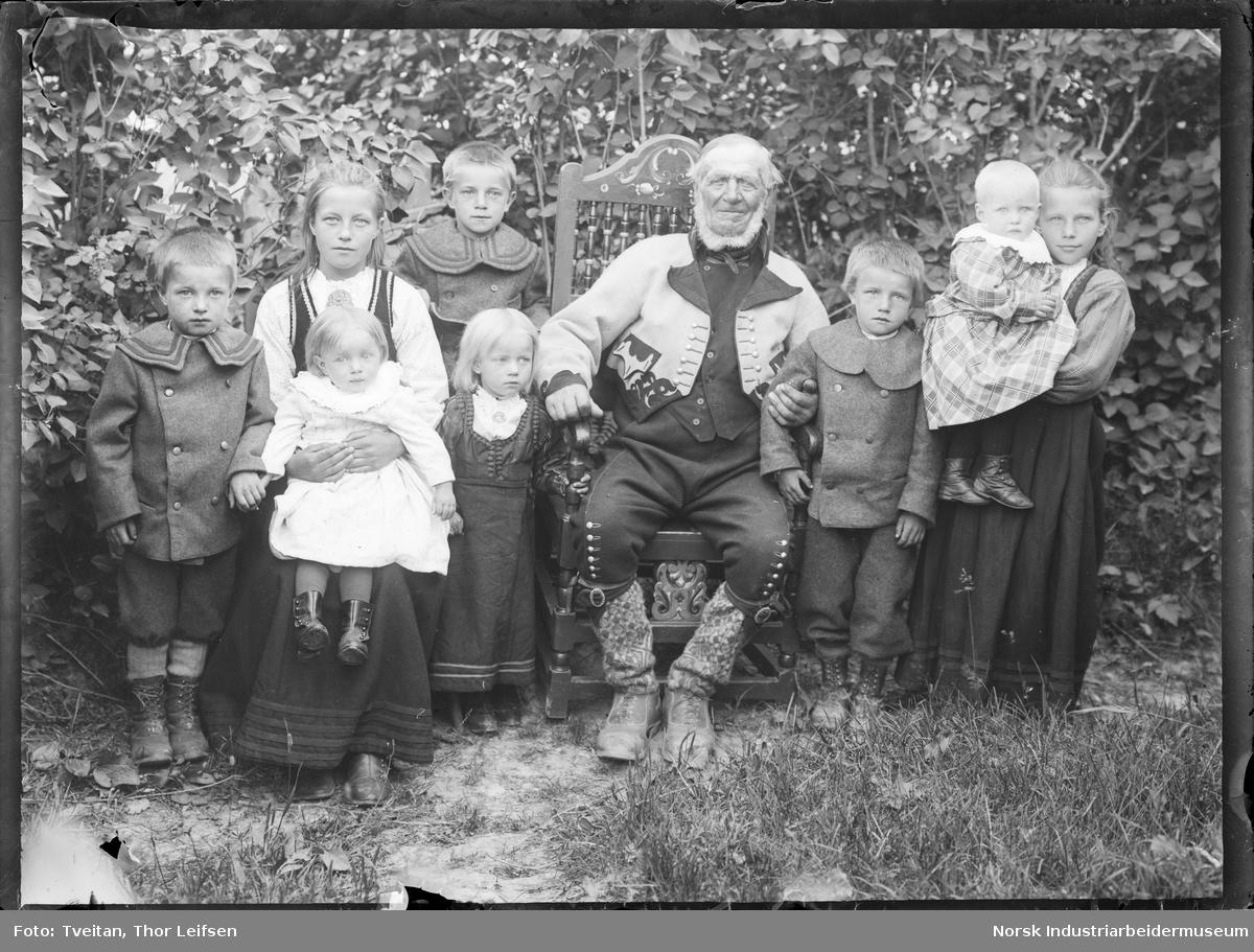 Gruppefoto. Eldre mann sittende på stol i bunad med barn rundt seg.
