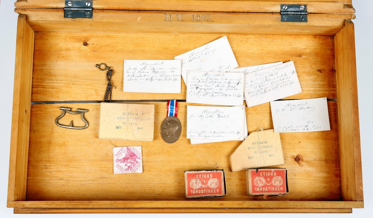 """Skrin formet som en bok og som inneholder samling med emblemer, luemerker, jakkemerker o.l. til ulike uniformer, for eksempel til en artilleristkepi og """"Livgardens Bjørneskindslue"""". Nederst ligger det adgangskort, som er trykket og som Helge Væringsaasen har skrevet på"""