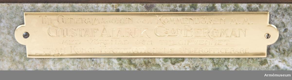 """Modell i silver tillverkad av C.G. Hallberg 1910 föreställande pontoner med tillbehör till krigsbro m/1875.  På sockeln en skylt med inskription: """"Till generalmajoren och kommendören m.m. Gustaf Alarik Cson Bergman med vördnad och tillgifvenhet från Kungl. Fortifikationens underofficerare"""".  Märkt. C.G. Hallberg H7 (se nedan).  Består av: från vänster på bilden Mellanponton m/1875 Stävponton m/1875 2 ankare med linor 2 underslagsregel med dubb 1 undeslagsdyna 1 drejare för ankartågets fastgörande 1 bockben 1 båtshake 2 linor 6 åror  2010-12-03 EW  Modellen är märkt med silverstämplar: CG Hallberg, tre kronor (sk kattfot), årsbeteckning  H7 (1910) samt ortsmärke för Stockholm (troligen s:t Erik). Dessa finns på: skylten, stävpontonen, mellanpontonen, underslagsreglarna och kanske på fler ställen. 2020-02-28 EW"""