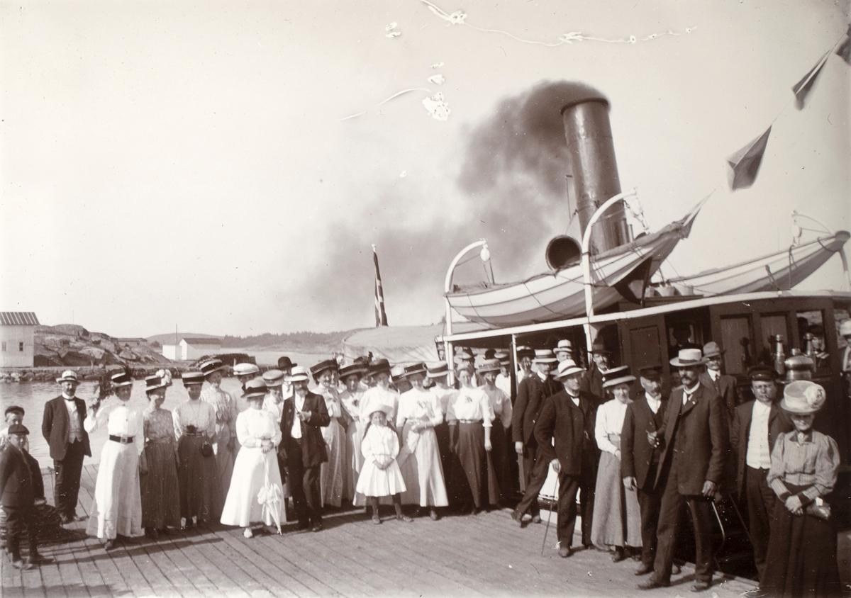 Gruppeportrett av flere mennesker på kaia ved Færder fyrstasjon. I bakgrunnen er dampbåten som gikk til øya.