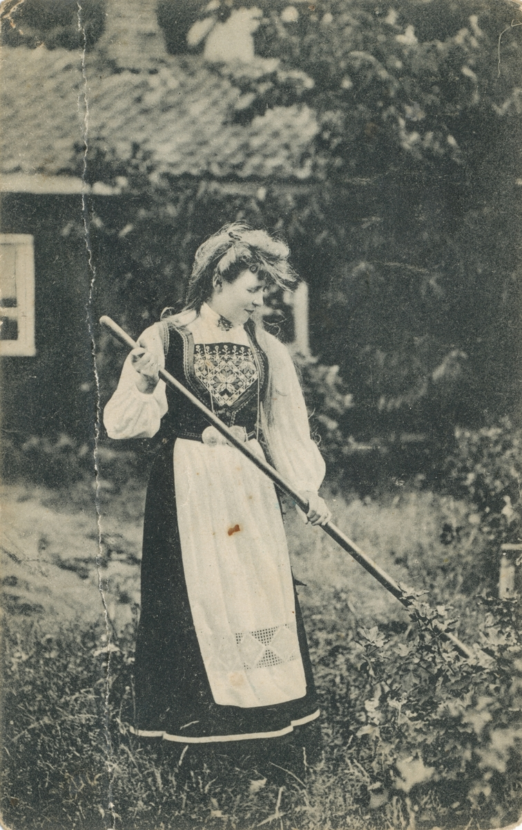 Postkortmotiv av ei kvinne i bunad som står i gresset og holder et redskap.