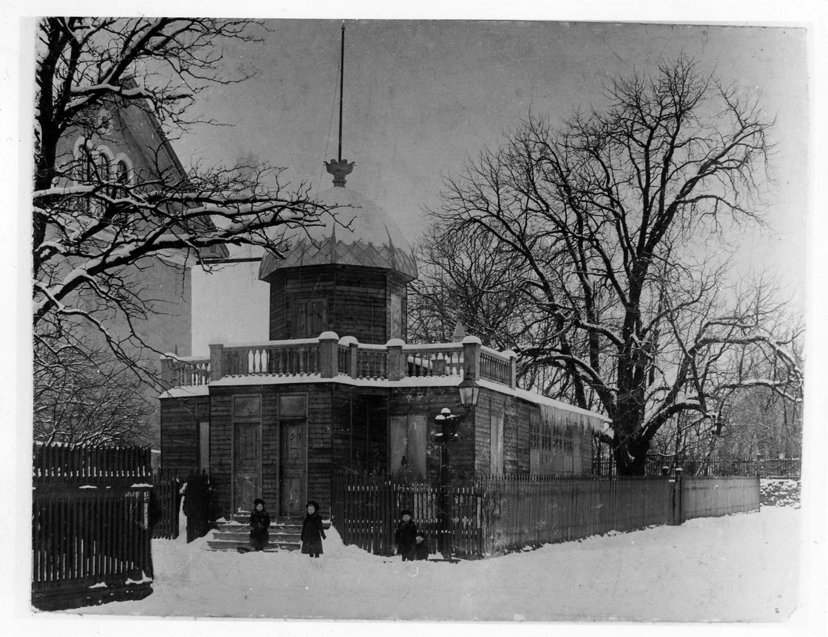 Bild tagen vintertid på Engblads Fotoateljé, en avlång byggnad med en tillbyggd kupol. Ateljén låg vid Alströmska magasinets norra gavel mot Lilla torget. Utanför ingången ses 4 barn. Mark och träd är snötäckta.