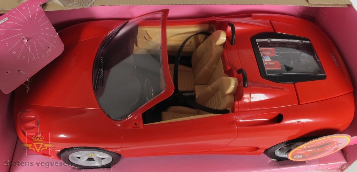 Miniatyr, lekebil i eske. Bilen er rød med svarte detaljer. Mangler venstre sidespeil. Esken er rosa med merkevarelogoer for Barbie, Mattel og Ferrari. Esken har et plastikkvindu slik at bilen er synlig fra utsiden, på vinduet står det skrevet fashion show.
