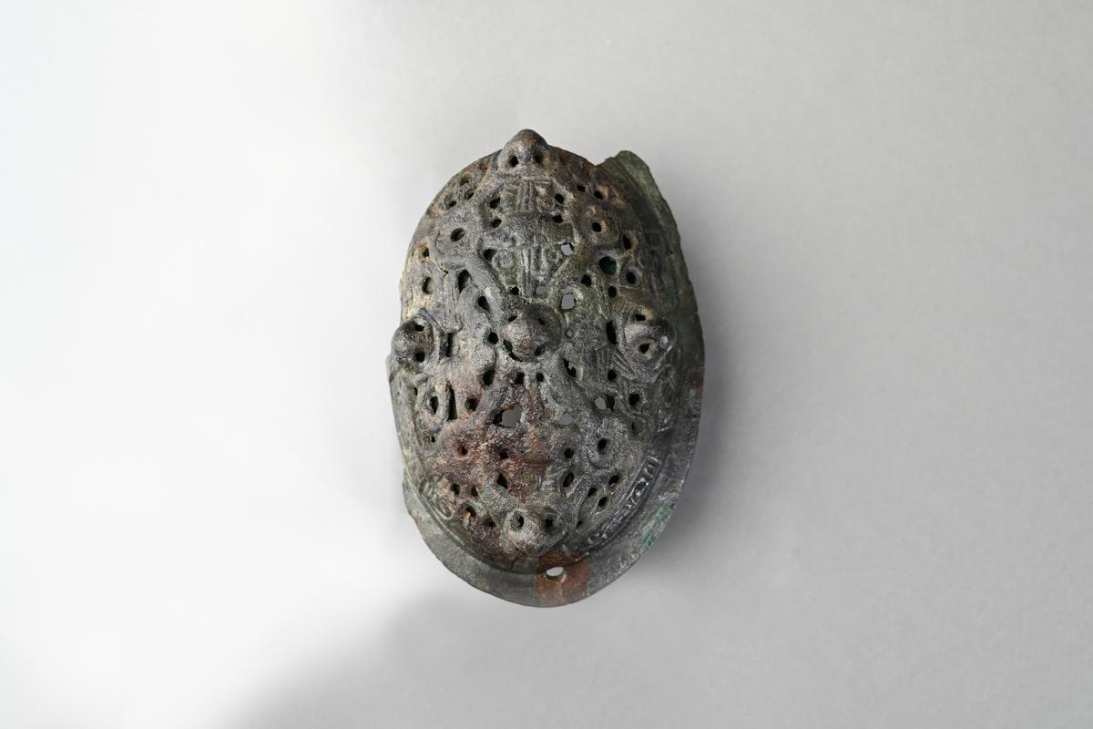 Spännbuckla (se Petersen fig 51) med genombruten överskålla med fem knoppar. Överskållan hel, separerad från underskållan. Underskållan skadad, ornerad längs kanten. Nålfäste och nålhållare kvar, men ej nålen. Tygavtryckmärken från gjurtformen på undersidan, troligen från linne vävt i tuskaft.