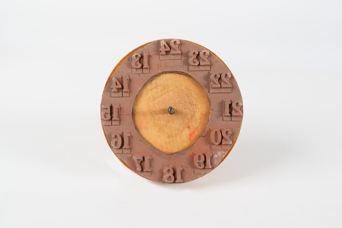 Stämpel av trä och gummi för 24-timmarsklocka, bestående av rund platta och handtag. Stämpeldynan är i form av en rosa gummiring med upphöjda siffror 13-24. Lodrätt genom handtaget och träplattan sitter en rund järnten.