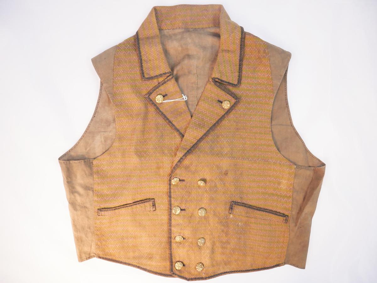Dobbelspent vest med nedslagskrage og slag - nyrokkokko-snitt.+ Langt framovertrekte sidesaumar og skuldersaum (truleg for å utnytte stoffet). Bua og spissa i nedkant. Skrå lommestolpar. Merke etter spenne i ryggen. Saum midt i ryggen. Framkantar, slag, krage og lommestolpe kanta med brunt og svart band i silke og bomull. 8 kuvne knappar i metall, truleg messingblekk (har vore 10).