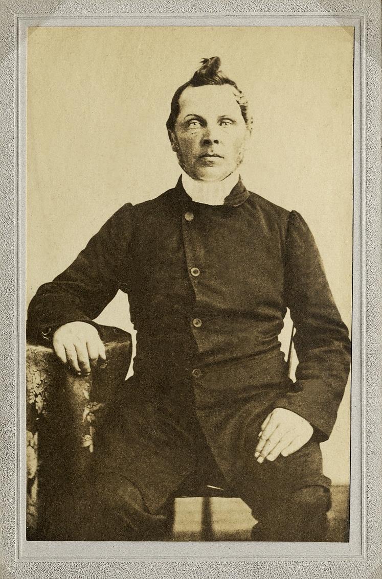 Foto av en man i prästrock och prästkrage m.m. Bröstbild, halvprofil. Ateljéfoto.