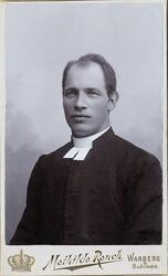 Foto av en man i prästrock med prästkrage m.m. Bröstbild, ha