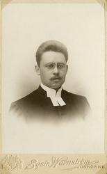 Foto av en man med mustascher och glasögon, klädd i prästroc