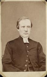 Foto av en man i prästrock och prästkrage. På västen skymtar