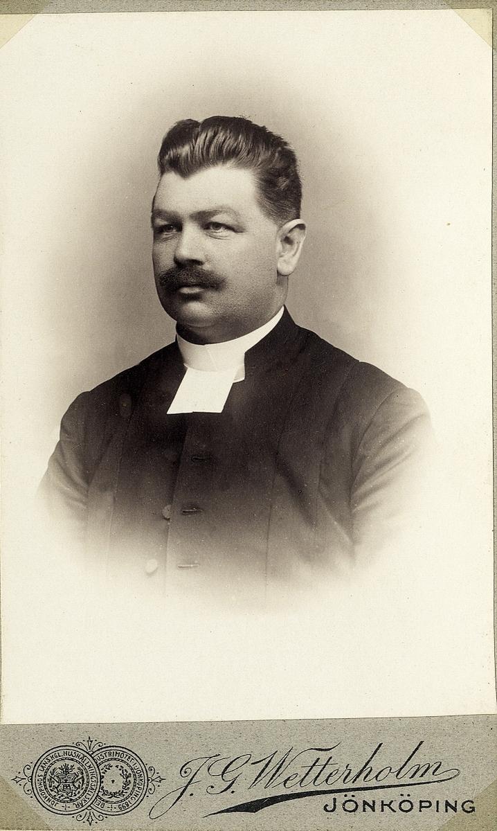 Foto av en man med mustascher, klädd i prästrock med prästkrage. Bröstbild, halvprofil. Ateljéfoto.