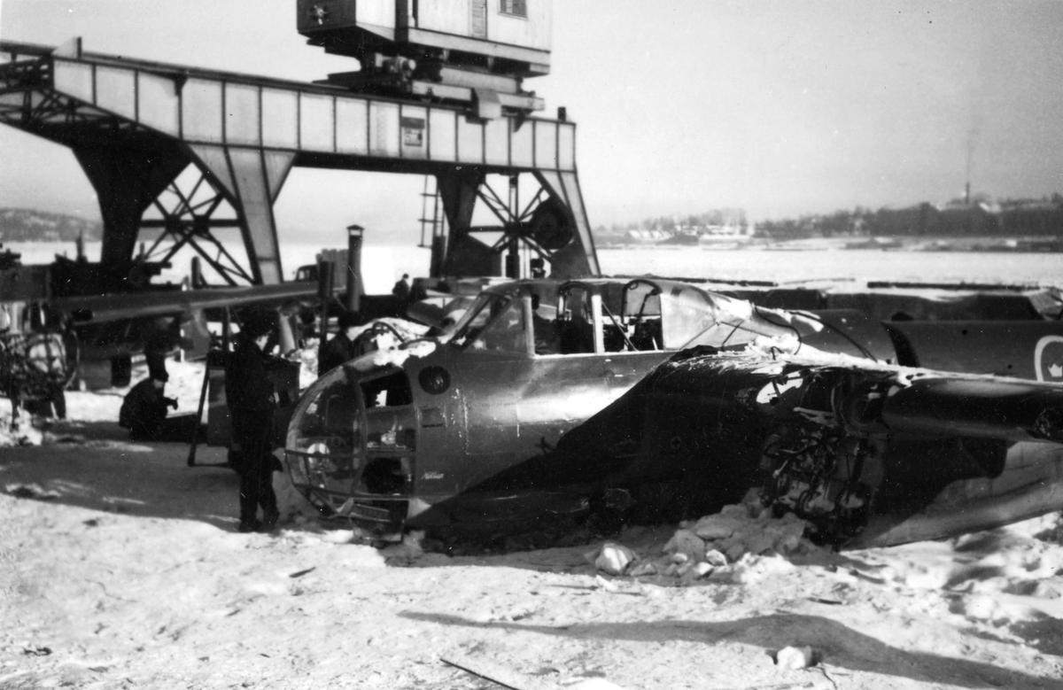 Två bärgade flygplan B 18 ligger på kajen i Härnösands hamn efter nödlandning på isen den 10 februari 1946. Motorerna har demonterats. I bakgrunden syns en lyftkran som användes vid bärgningen.