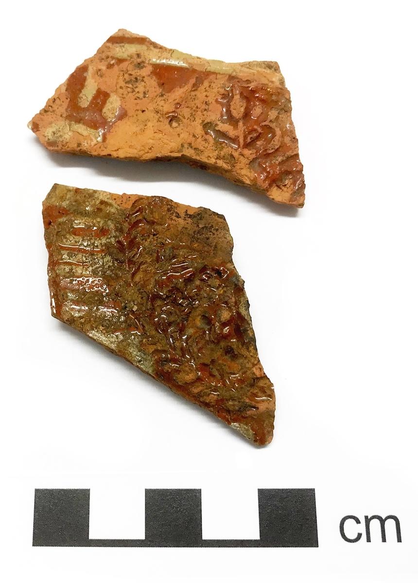 Relieffdekor med krans, röd och grön glasyr och vitlerränder. Troligen tysk import tillverkad i slutet av 1500-talet. 5 fragment Kontext: A36