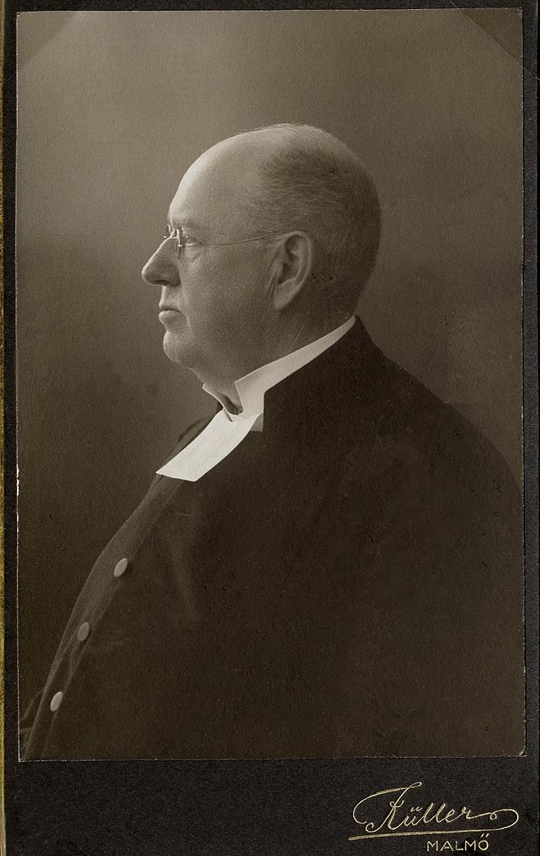 Foto av en man med glasögon, klädd i prästrock och prästkrage.  Midjebild, profil. Ateljéfoto.