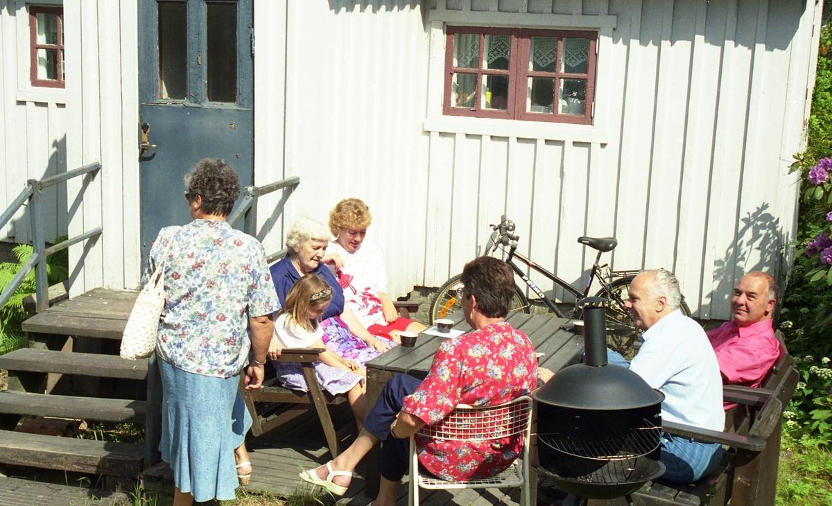 """Invigning av Ekebackens Hantverksgård (tidigare John Lindströms möbelsnickeri) på Gamla Riksvägen 81, början av 1990-talet. Besökare sitter och fikar utanför """"Lillstuga""""."""