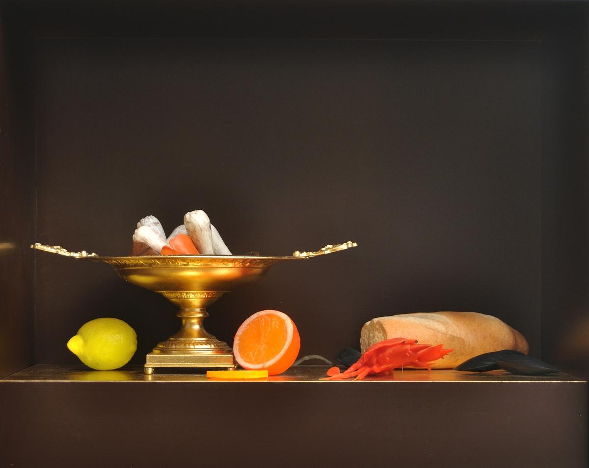 """Objekt, """"Stilleben med krabba"""" av Thomas Olsson. Rektangulär omålad fanerlåda innesluten i plexiglashuv. Ena långsidan """"öppen"""" med bara plexiglas. Inteiören svartmålad med guldfärgad bottenplatta. På denna högt fat, krabba, musslor, painriche, svampar och frukter. Till det hela är anslutet en fotpedal som får krabba att lyfta sig (med el ansluten). Se bilaga."""