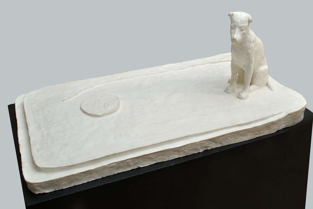 """Skulptur i gips, """"Mitt oroliga hjärta"""" av Bianca Maria Barmen. Låg, rektangulär sockel med liggande papyrusblomma och korvskiva. I ena hörnet en sittande hund.  Osignerad."""