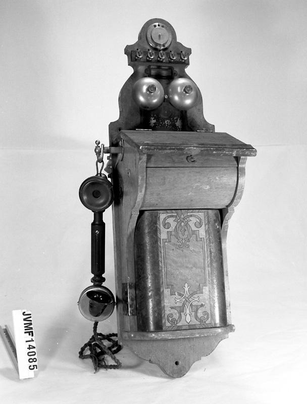 Väggtelefon av trä och plåt. Två ringklockor upptill på framsidan. Telefonlur i vänster sida. Telefonskåpet är dekorerad med intarsia i olika träslag på framsidan.