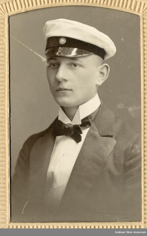 Porträtt av Karl Petersson, klädd i studentmössa, mörk kavaj, vit skjorta mörk fluga.