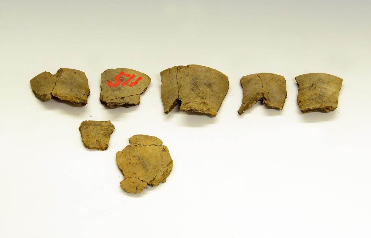 Fra protokollen:  her foreligger ennå et leirkar (under SM.0511), et lite beger i fragmenter, noe nær Bøe: Jernalderens keramikk, fig. 188. Hverken form eller dekor kan bestemmes nærmere ut ifra de små bitene som foreligger. Feilnummerering, dette kar hører vel neppe til resten av funnet, dog kan det passe inn i tid. Yngre romertid, 4. årh.
