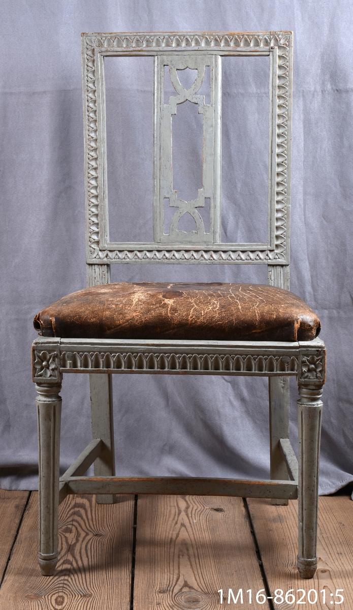 Gustaviansk stol med svarvade framben med hörnfleuron och kannelyrer, raka bakben sarg och rygg med så kallad nagelskärning. Genombruten rygg med horisontell bricka så kallad Gunnebobricka, stoppad lös sits, klädd med oxhud.