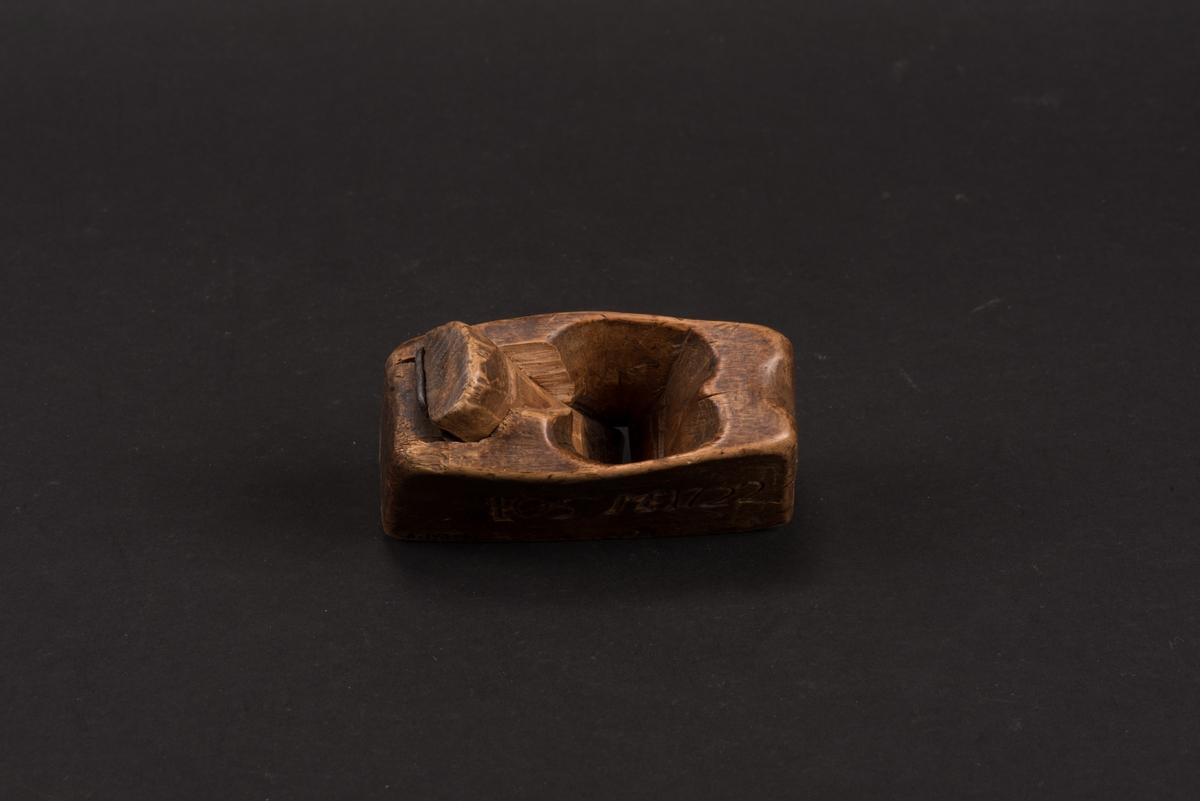 Liten profilhyvel av trä. Hyveljärn av stål. Stockens hål för hyveljärn och kil är utsnidat. På sidorna inristat bomärket samt initialer och årtal.